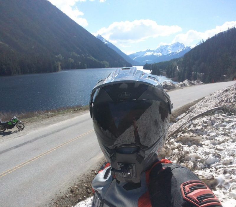 A person wearing a motorcycle helmet taking a selfie in front of Duffey lake in British Columbia, Canada
