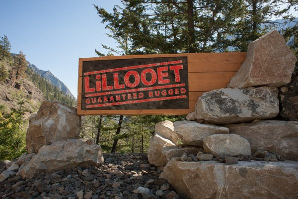 A large lillooet sign on the side of the road surrounded by rocks and mountains heading into the town of lillooet