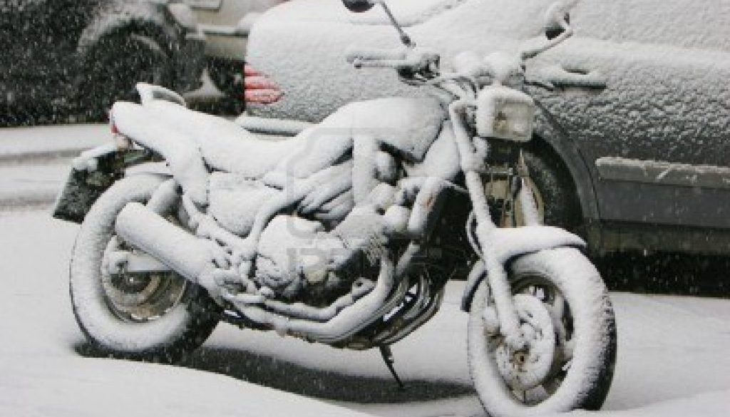 A motorcycle that is covered in snow sitting outside in the cold