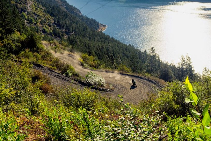 A single motorcycle kicking up dust on a windy dirt road above blue seton lake