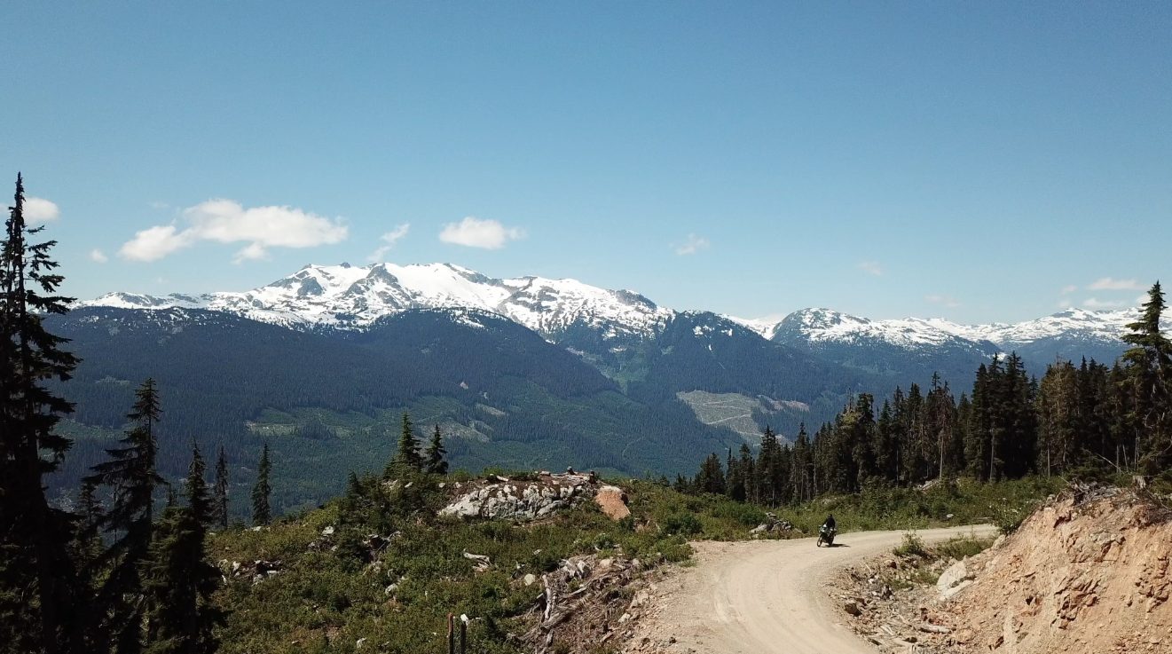 Motorcycle riding up a dirt road surrounded by mountains in between whistler and pemberton