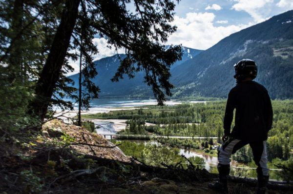 Motorcycle rider with back facing, looking out over Lillooet Lake Moto Experience Adventure Info