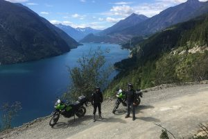 guys standing above anderson lake on the highline with motorcycles